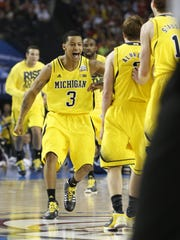Michigan's Trey Burke greets teammates Spike Albrecht after Albrecht hit a three point shot during the 2013 NCAA championship game between Michigan and Louisville at the Georgia Dome in Atlanta on Monday, April 8, 2013.