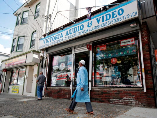 Pedestrians pass by Victoria Audio and Video, the site where in 1993 store employee Tito Merino was murdered during a robbery, in Paterson, N.J.