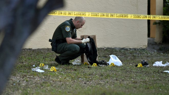 Indian River County Sheriff's Office crime scene Detective Christian Yanchula investigates evidence from a shooting Thursday, Dec. 8, 2016 on Kennedy Court  at the Victory Park Apartments in Gifford.  CQ: Christian Yanchula