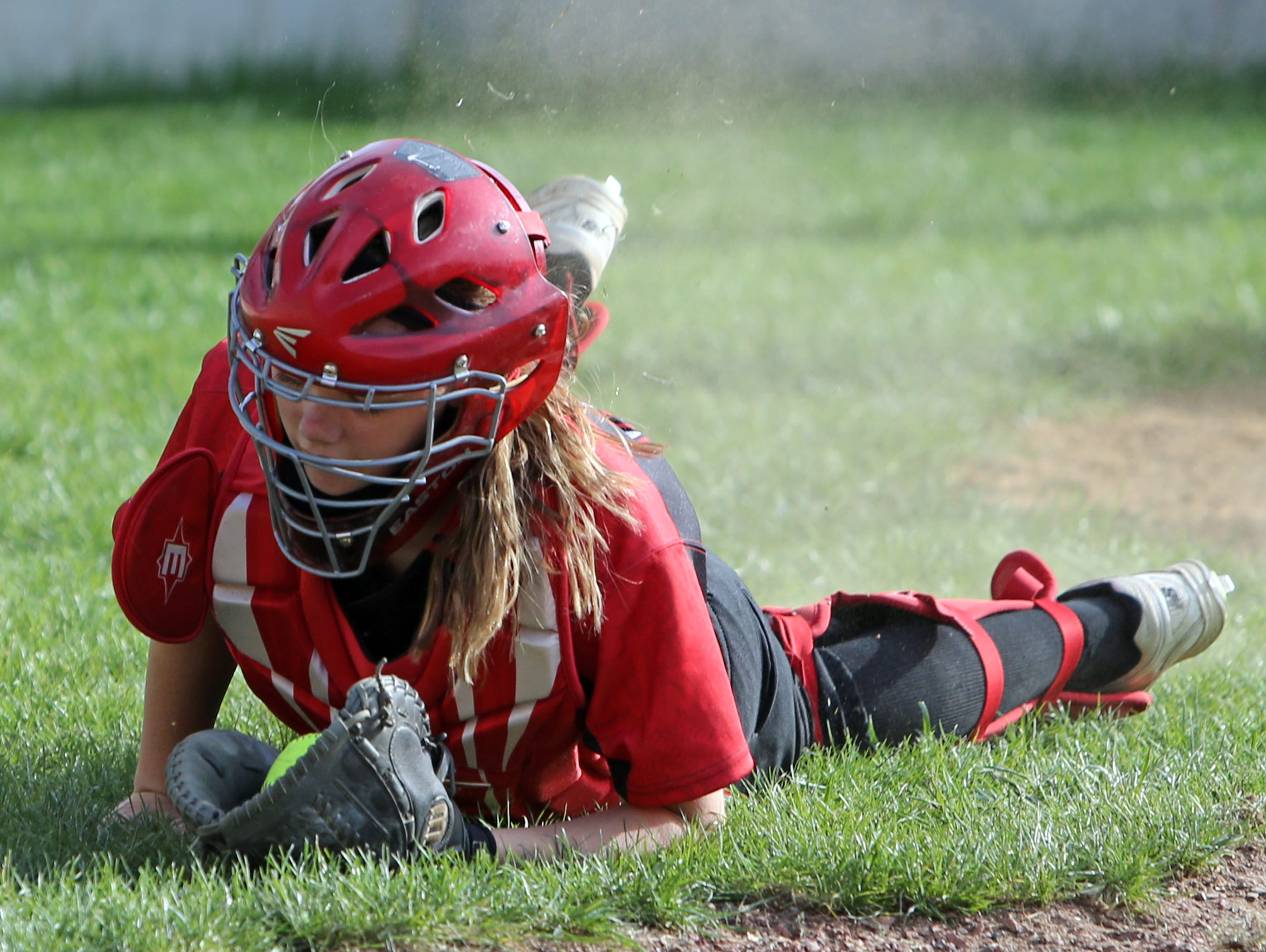 Milford Catcher Kelsey Seitz makes a diving catch of a pop foul.