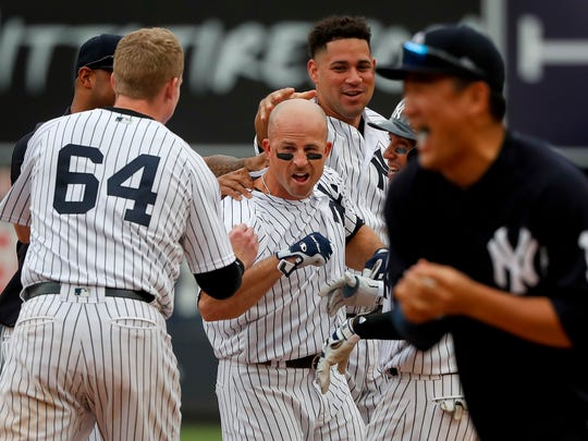 New York Yankees' Brett Gardner, center, is mobbed by teammates after batting in Jacoby Ellsbury for the wining run against the Tampa Bay Rays during the ninth inning of a baseball game, Saturday, July 29, 2017, in New York. The Yankees won 5-4.