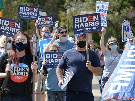 People walking east on West Sixth Street, in support of Joe Biden and  Kamala Harris, pass a few supporters of President Donald Trump, right.