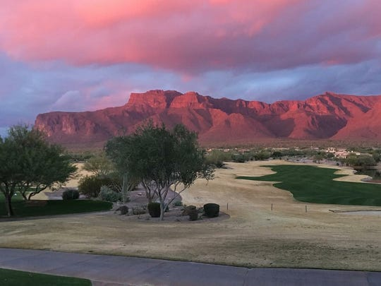 The view of the Superstition Mountains and golf course at sunset.