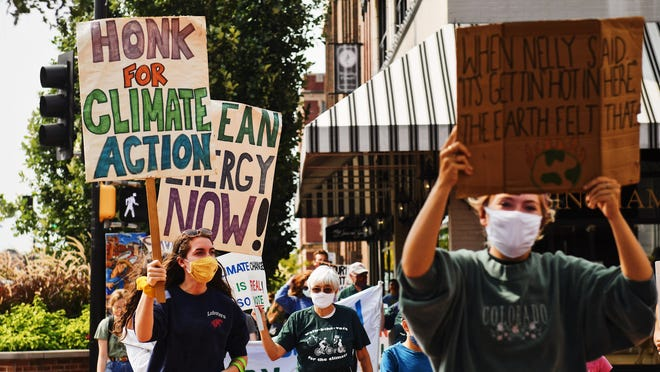 Activists march down the sidewalks of downtown Columbia during the Walk for Climate 5K on Sunday afternoon.