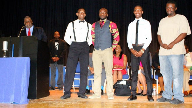 Timothy Hopkins, vice president of the Poughkeepsie Chapter of Kappa Alpha Psi, presents scholarship awards to from left, Demaj Ffriend, Ivan Moolt-Moolt, Terrell Vassell and Jawaan Walter. Left to right back row, are Da'Ron Wilson, assistant principal of Poughkeepsie High School and Dr. Nicole Williams, Superintendant of Schools.