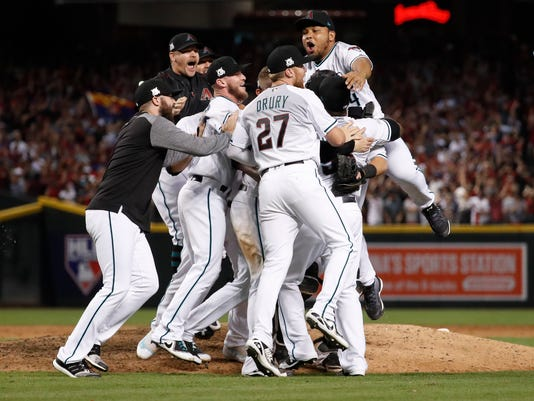 The Arizona Diamondbacks celebrate after the National League wild-card playoff baseball game against the Colorado Rockies, Wednesday, Oct. 4, 2017, in Phoenix. The Diamondbacks won 11-8 to advance to the NLDS against the Los Angeles Dodgers. (AP Photo/Matt York)
