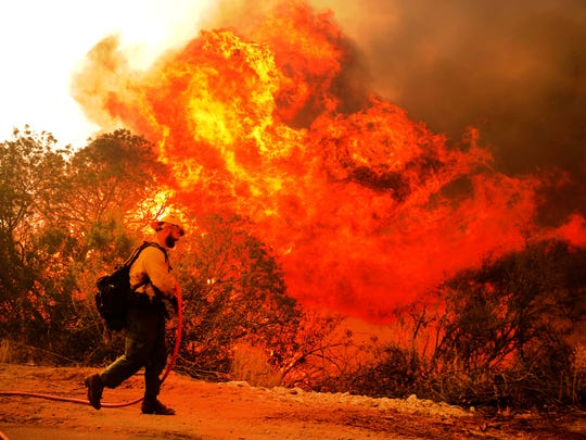 Crews battled the Thomas Fire on Saturday at De La Garrigue Road and Highway 150 near Ojai, but when the the flames grew too big, they had to run. The blaze continued to burn strongly toward homes in that area on Saturday.