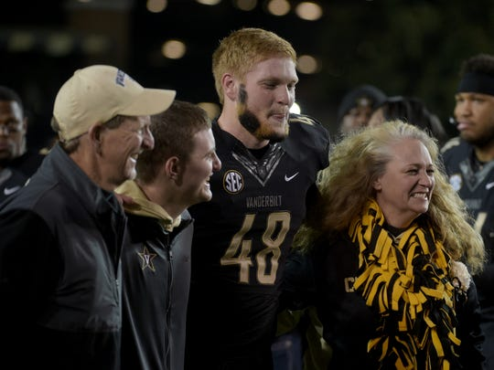 Vanderbilt long snapper Jacob Schultz (48) is surprised on Senior Night by his brother, Navy Ensign Josh Schultz, who returned from Iraq before the game against Tennessee at Vanderbilt Stadium Saturday, Nov. 26, 2016, in Nashville, Tenn. His parents, Jack and Kristine Schultz, of Murfreesboro, join him on the field.