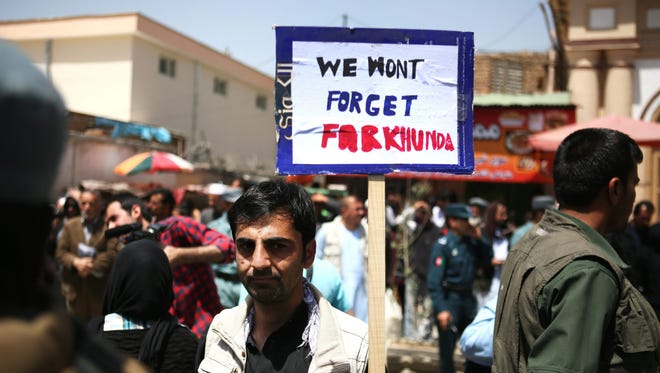 An Afghan holds a placard during a protest demanding justice for woman beaten to death by a mob, in Kabul, Afghanistan, 27 April 2015.