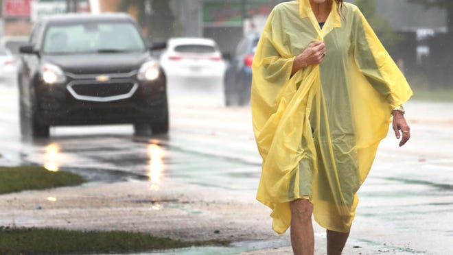 A woman walks along Mason Avenue in a light rain Thursday. There were heavy rains at times on Thursday and more wet weather could be on the way for the weekend, a forecaster said.