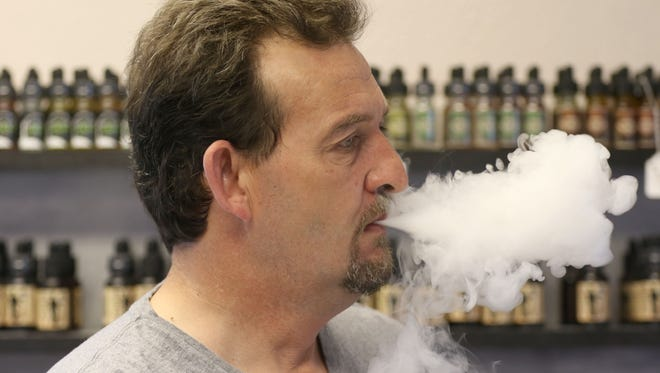 Jubel Arnold, co-owner of Central City Vapors in Marshfield, blows vapor out while vaping in the store March 29, 2016.