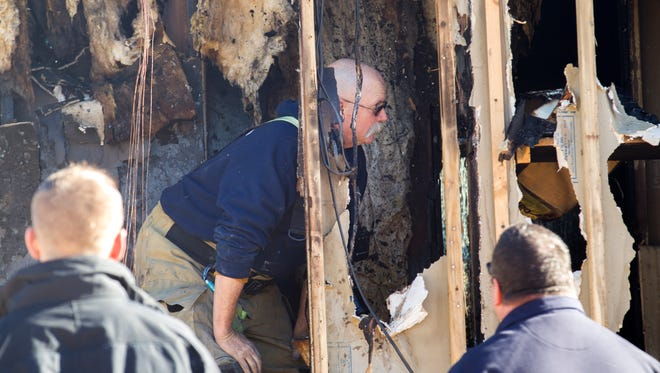 San Juan County Fire and Explosion Task Force members investigate the scene of a house fire on Thursday in Kirtland.