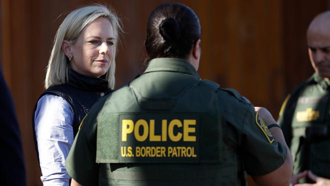 U.S. Department of Homeland Security Secretary Kirstjen Nielsen, left, speaks with Border Patrol agents near a newly fortified border wall structure Friday, Oct. 26, 2018, in Calexico, Calif.
