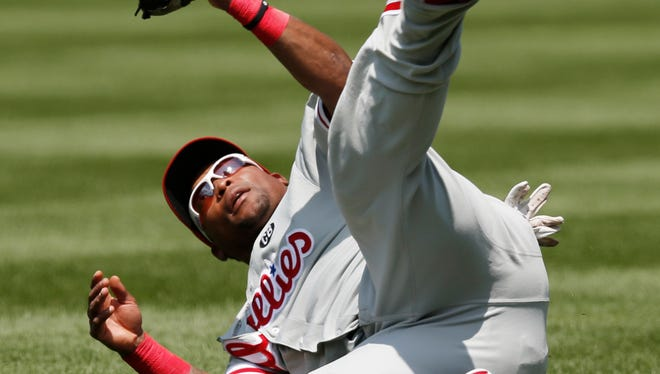 Philadelphia Phillies right fielder Marlon Byrd (3) tumbles over after making a sliding catch of David Wright's third-inning line out in a baseball game in New York, Wednesday, July 30, 2014. (AP Photo/Kathy Willens)