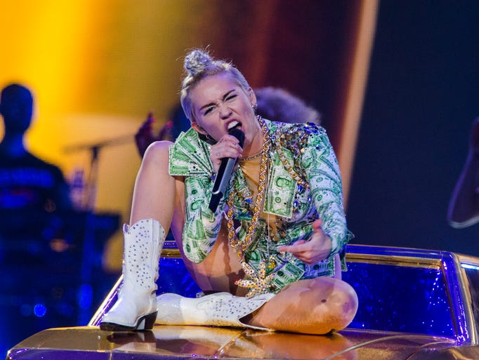 "Miley Cyrus performs Thursday, Aug. 7, 2014, at Bridgestone Arena in Nashville. The show, part of her ""Bangerz"" tour, was rescheduled from April after she was hospitalized for a ""severe allergic reaction."""