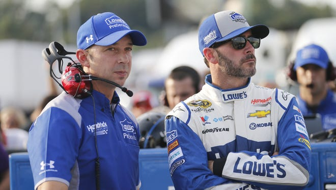 Jimmie Johnson waits with crew chief Chad Knaus as they wait for NASCAR Sprint Cup qualifying at Richmond International Raceway in Richmond, Va., Friday, Sept. 9, 2016.