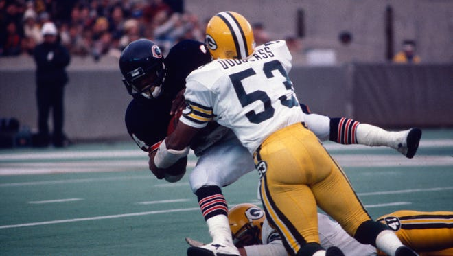 Green Bay Packers linebacker Mike Douglass goes high and safety Tom Flynn goes low to stop Chicago Bears running back Walter Payton during Green Bay's 20-14 victory at Soldier Field in Chicago on Dec. 9, 1984.