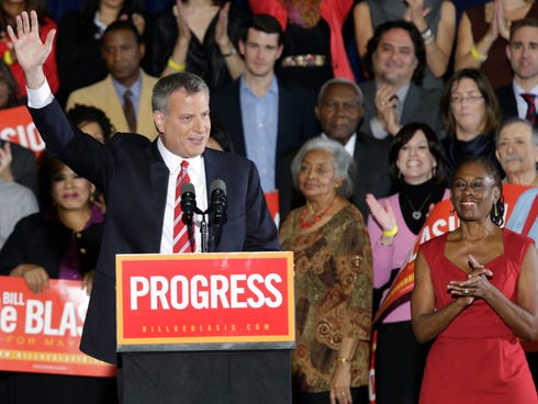 Democratic Mayor-elect Bill de Blasio, flanked by daughter Chiara, left, and wife Chirlane, waves from the stage after he was elected the first Democratic mayor of New York City in 20 years.