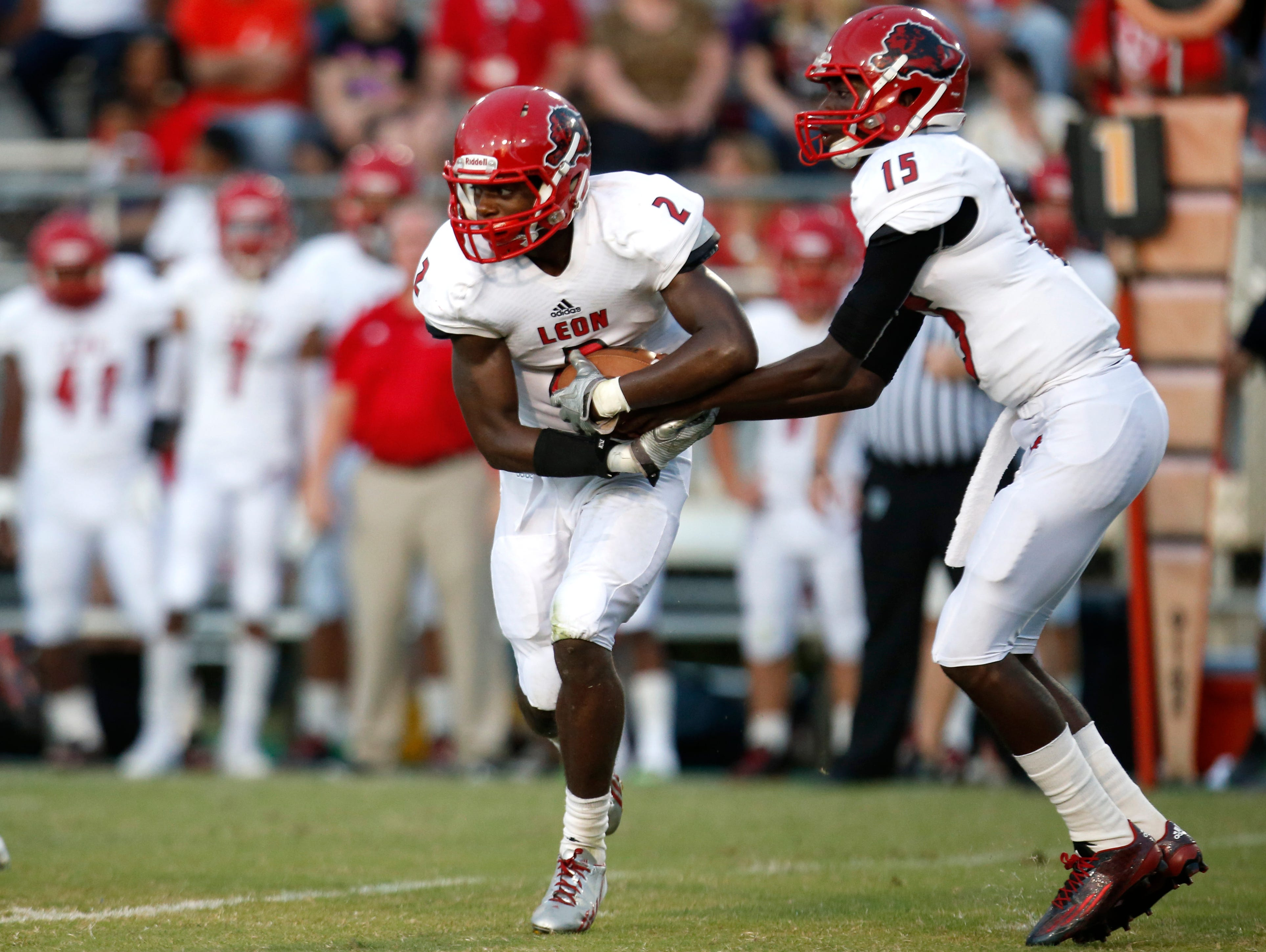 Leon quarterback Tyhran Glasco hands off to James Peterson against Godby at Cox Stadium on Friday.