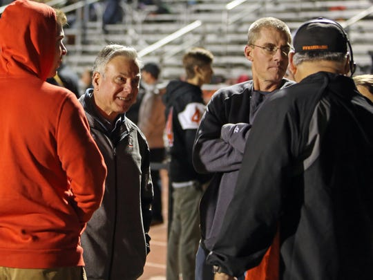 Former Anderson head Coaches Vince Suriano [left] and Jeff Giesting [right] talk to TV crews before the playoff game between the Troy Trojans and the Anderson Redskins at Anderson High School, November 3, 2017.