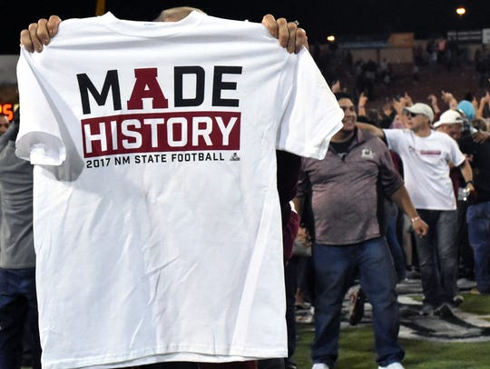 An Aggie football fan holds up a t-shirt that says