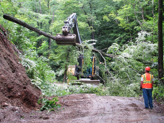 A Town of Chemung highway crew removes trees along Doolittle Road in preparation for a widening project. The town is temporarily laying off all six of its highway employees.