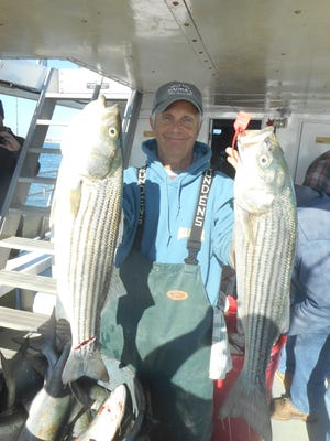 George Cullen, from Sparta, with a pair of keeper striped bass he caught on the Sea Hunter.