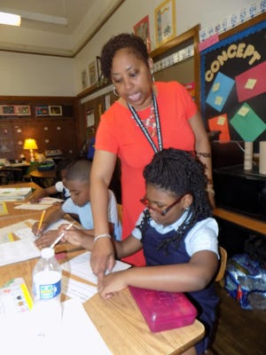 Mitzi Davis of Novi instructs Sakaria Smith, a second-grade student at Thirkell Elementary-Middle School in Detroit.