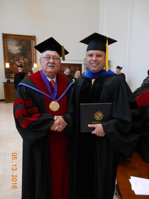 Nelson T. Newman, right, accepts his doctoral degree form Louisiana Baptist University President Neal Weaver.