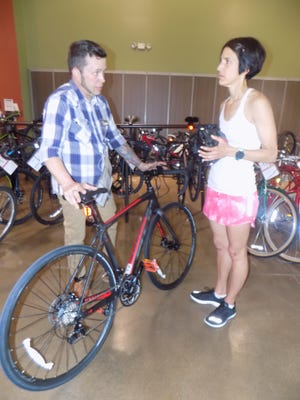 Dwayne Gillmore speaks with Lisa Hurley about her recent purchase at Performance Bicycle in Novi. Gillmore commutes 16 miles by bike to the shop, traveling main roads. Hurley avoids biking on roads due to fear of distracted drivers.