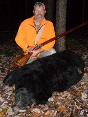 The author poses with a 350-pound bear he shot with a flintlock rifle during Maryland's 2016 bear season.