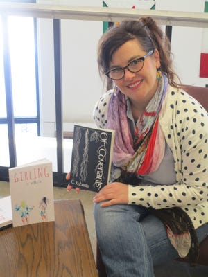 """Christina Kubasta poses with her novel """"Girling"""" and her book of poetry """"Of Covenants"""" in Marian University's Cardinal Meyer Library. Both are now available."""