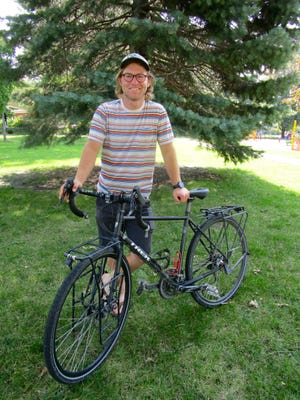 Taylor Mighell recently received his PhD from a university in Portland, Ore., and celebrated by biking to his home in Geneseo. Photo by Claudia Loucks