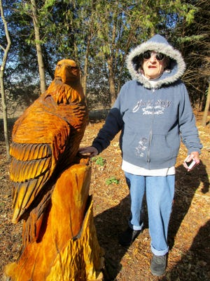 Doris (Skipper) Snow stands by the carved American eagle that is now in place in her yard, on the stump of the tall Cedar Tree that was blown over in a summer storm. Photo by Claudia Loucks