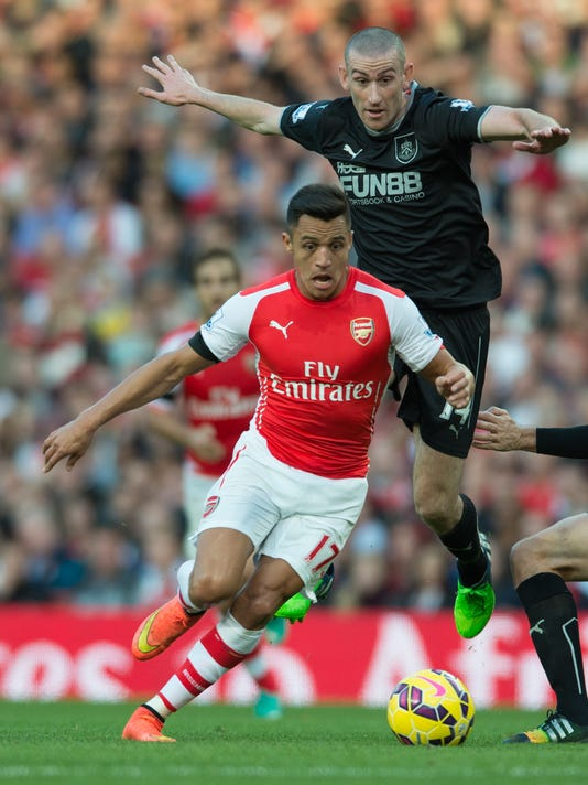 Arsenal's Alexis Sanchez, front, competes for the ball with Burnley's David Jones, back, during their English Premier League soccer match at the Emirates stadium, London, Saturday, Nov. 1, 2014. (AP Photo/Tim Ireland)