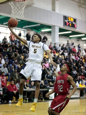 Northwestern's Kylan Shipp (32) watches as East English Village's Chris Rollins (5) goes for the layup during the Northwestern vs. East English Village boys' basketball semifinals on Friday, Feb. 12, 2016 at Cass Technical High School in Detroit. East English Village beat Northwestern 71-70.