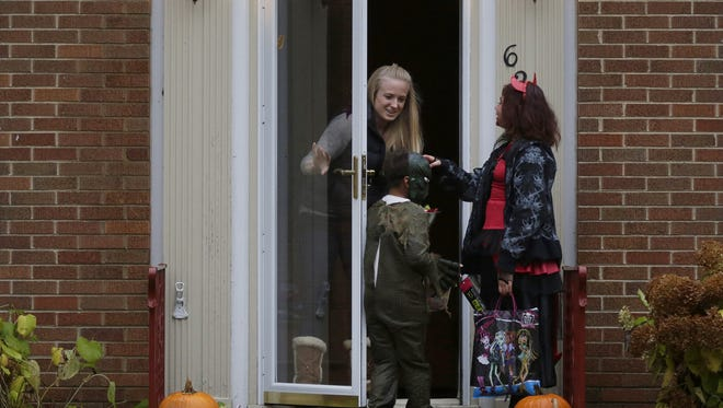 Alicia Santella hands out candy as Halloween trick-or-treaters roam the streets of Appleton on Oct. 31, 2015.