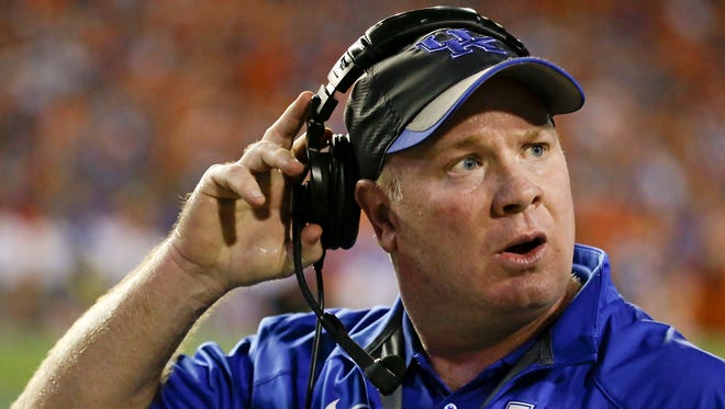 Kentucky head coach Mark Stoops talks with assistants on the sideline during the first half of an NCAA college football game against Florida in Gainesville, Fla., Saturday, Sept. 13, 2014. (AP Photo/John Raoux)