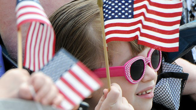 Izabel Gibson, 5, of Ontario, show her patriotism by waving a flag during the Memorial Day parade.