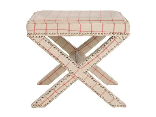 This photo provided by Overstock.com shows a Safavieh Palmer checkerboard ottoman. Using just a touch of color is a good way to introduce a strong hue; the checkerboard pattern highlights the accent of red in this Safavieh Palmer bench from Overstock. Nickel nail head trim dresses up the piece.