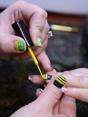 Patti Wagnitz paints Kendra Jones' nails with Packers colors at Creative Hair Designs.