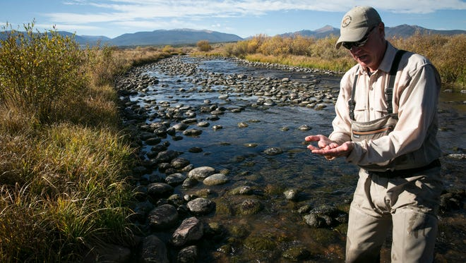 In this Thursday, Sept. 29, 2016 photograph, Kevin Scannel, a fishing guide at Devil's Thumb Ranch near Tabernash, Colo., looks over bugs taken from the Fraser River. Some conservationists and environmental groups are crying foul while others are willing to compromise as Denver Water looks to exercise its water rights on the Fraser River. (Nathaniel Minor/Colorado Public Radio via AP)