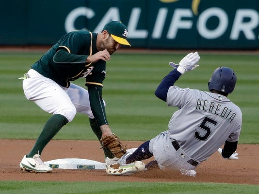 Oakland Athletics shortstop Adam Rosales, left, tags out Seattle Mariners' Guillermo Heredia (5) at second base on a steal attempt during the first inning of a baseball game Friday, April 21, 2017, in Oakland, Calif. (AP Photo/Marcio Jose Sanchez)