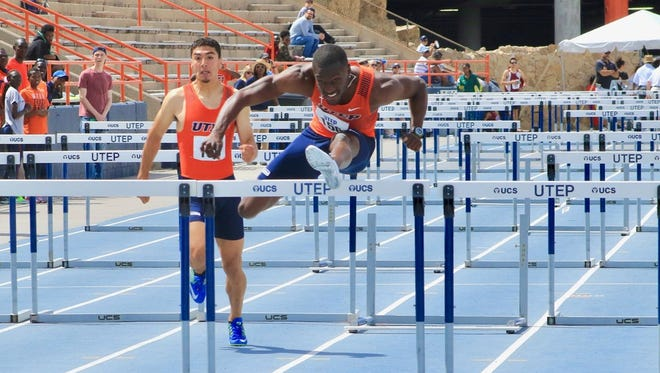 Shakeem Smith is shown in action, leaping over a hurdle.