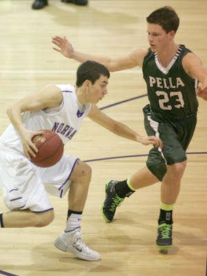 Norwalk senior Grant Wright is defended by Pella junior Seth Johnson during a Jan. 14 game in Norwalk. Norwalk lost 73-54.