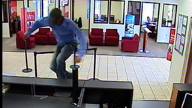The suspect can be seen jumping over the counter in this still image from surveillance video.