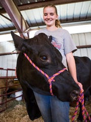 Jordan Taylor, 19, poses with her first show heifer, now eight years old, who she raised on a bottle at the Augusta County Fair on Tuesday, August 4, 2015.
