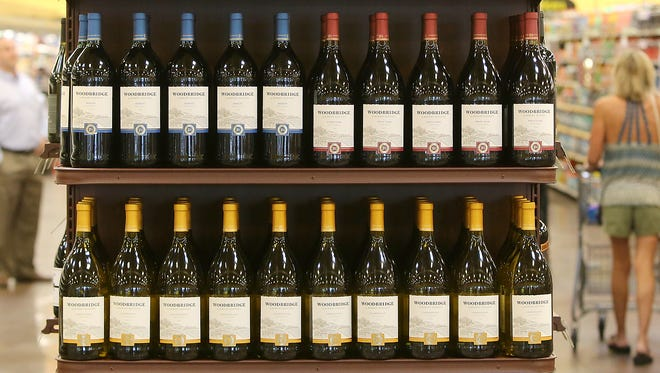 Customers are seen on both sides of the wine aisle at Kroger on University Parkway in Jackson, on July 1.