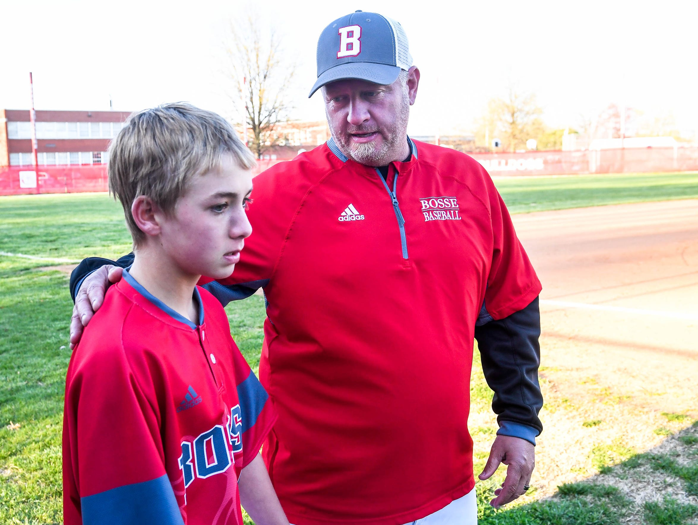 Bosse coach Craig Shoobridge talks with Reese Perry (5) after his at-bat against Castle on Thursday.