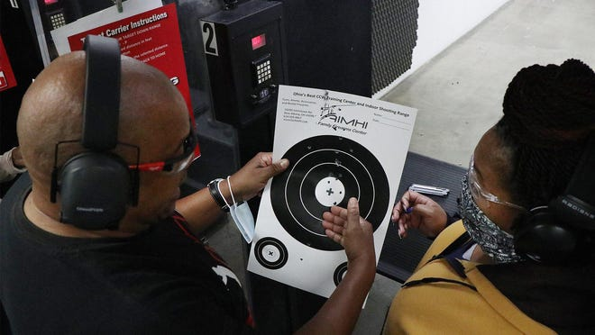 Onyx Gun Club co-founder and NRA-certified instructor Thomas Cunningham, left,  talks with Ericka Jackson, of Toledo, during a lesson on Aug. 8 at AimHi shooting range in New Albany.